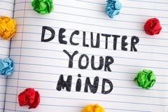 Uttryck Declutter som din mening på anteckningsbokarket med färgrikt skrynkligt papper klumpa ihop sig runt om det royaltyfri foto