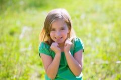 Uttryck för gest för blond ungeflicka upphetsat i grönt utomhus- Royaltyfria Bilder