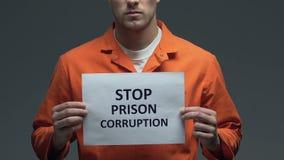 Uttryck för stoppfängelsekorruption på papp i händer av den Caucasian fången stock video