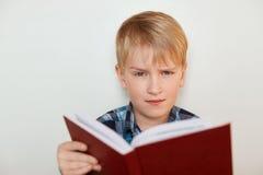 Uttryck och sinnesrörelser för mänsklig framsida Barn och utbildning En närbild av den attraktiva pysen med ganska hår som läser  arkivbilder