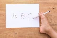 Uttrycka abc:et i vitbokhandstil vid den högra foten av rörelsehindrad peop Royaltyfri Foto