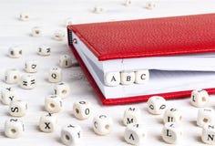 Uttrycka abc:et som är skriftligt i träkvarter i röd anteckningsbok på vit woode Arkivbild