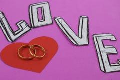 Uttrycka förälskelse på rosa bakgrundsbakgrund med hjärta och förlovningsringar royaltyfri foto