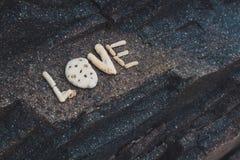 Uttrycka förälskelse som göras av samlade skal på en granitsten Royaltyfria Bilder