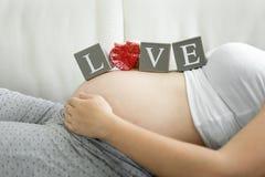 Uttrycka förälskelse som stavas på kvarter på gravid kvinnamagen Royaltyfria Bilder