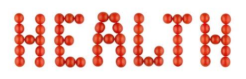 Uttrycka HÄLSA som göras från röda tomater på den vita bakgrunden royaltyfri fotografi