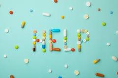 Uttrycka HJÄLP från kulöra preventivpillerar och kapslar på grön bakgrund Vilka mediciner som väljer bättre, vad ska hjälpa Arkivbild