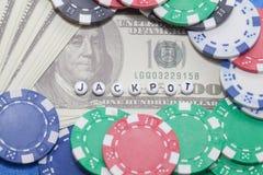 Uttrycka `-JACKPOTT` med pokerchiper och pengar royaltyfri fotografi
