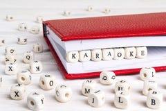 Uttrycka karaoke som är skriftlig i träkvarter i röd anteckningsbok på vit w arkivbild