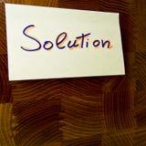 Uttrycka lösningen som är skriftlig på en gul postit som fästas på en wood panel - för begreppsmässigt bruk Royaltyfria Foton