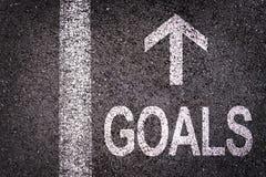 Uttrycka mål och en pil som är skriftlig på en asfaltväg Royaltyfri Foto