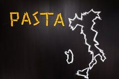 Uttrycka pasta som göras av torr pasta på den svarta bakgrunden med den skriftliga ramen av landet Italien av krita Arkivfoton