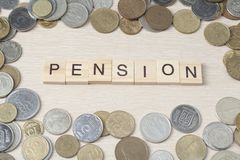 Uttrycka PENSIONEN på träkuben med ramen av mynt på wood bakgrund Budget- begrepp för pension Royaltyfri Fotografi