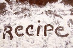 Uttrycka receptet som är skriftligt i vitt mjöl på trätabellen Royaltyfri Foto