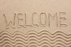 Uttrycka välkommet skriftligt på sanden Arkivbild