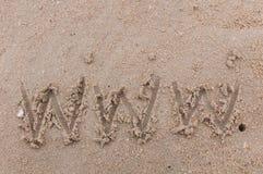 Uttrycka www som är handskriven i sand Royaltyfri Bild