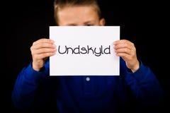 Uttrycker det hållande tecknet för barnet med danska ledsna Undskyld - Royaltyfri Fotografi