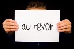 Uttrycker det hållande tecknet för barnet med franska Au Revoir - farväl Royaltyfri Bild