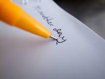 Uttrycker skriftligt genom att använda en penna Arkivbild