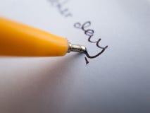 Uttrycker skriftligt genom att använda en penna Royaltyfri Foto