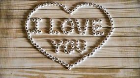Uttrycks`en älskar jag dig stor hjärta för ` som komponeras av vit, rundan, plast- kvarter på en träyttersida Royaltyfri Fotografi