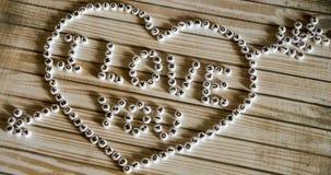Uttrycks`en älskar jag dig stor hjärta för ` som komponeras av vit, rundan, plast- kvarter på en träyttersida Arkivfoto