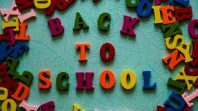 Uttrycks`en tillbaka till skola`-träkulöra bokstäver på tabellmintkaramellfärgen Royaltyfria Bilder
