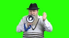 Uttrycksfull ilsken man som talar i megafon lager videofilmer