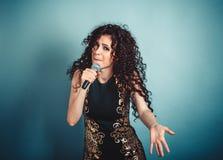 Uttrycksfull kvinnadamflicka som sjunger se dig med mikrofonen i handdans royaltyfria bilder