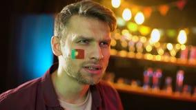 Uttrycksfull portugisisk fotbollfan med flaggan på kind som hurrar för landslag stock video