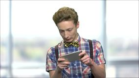 Uttrycksfull tonårig grabb som spelar leken på telefonen stock video