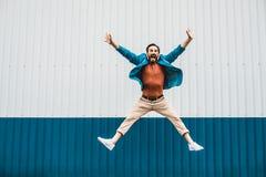 Uttrycksfull ung man som hoppar och ser lycklig royaltyfri foto
