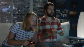 Uttrycksfulla par som hemma spelar videogamen arkivfilmer
