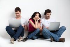 uttrycksvänner som rymmer bärbar dator tre Arkivfoton