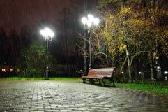 Utumn regnig natt med den ensamma bänken under gulnat landskap för höstträd-natt höst Arkivfoton