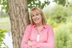 Utvändigt bära för mogen kvinna i rosa kläder arkivbilder