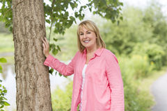 Utvändigt bära för mogen kvinna i rosa kläder royaltyfri bild