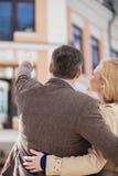Utvändigt för vuxna par stående och seende hus Arkivbild