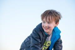 Utvändigt le för stilig ung pojke på den guld- timmen för solnedgång Royaltyfri Foto