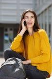 Utvändigt samtal för lyckligt sammanträde för kvinnlig student på mobiltelefonen arkivbild