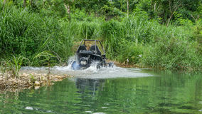 UTV off road four wheel drive. Sport car driving up the hill to the creek. Driving fun and safety Royalty Free Stock Images