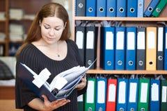 Utövande affärskvinna som ser dokument Arkivfoton