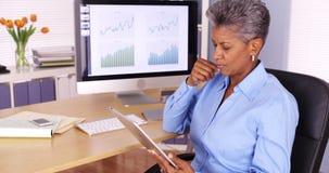 Utövande hög affärskvinna som arbetar på minnestavlan på skrivbordet Royaltyfri Bild