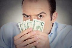 Utövande vdframstickande för girig bankir, hållande dollarsedlar Royaltyfri Fotografi