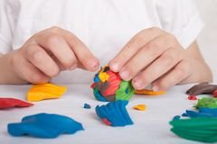 Utveckling av liten motorexpertis av barn Ett barn hugger en färgrik boll av plasticine arkivbilder