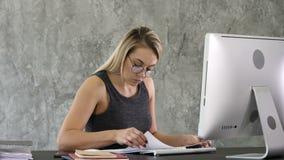 Utveckling myndighet, feminitybegrepp Den nätta affärskvinnan sitter på hennes ljusa moderna arbetsstation som kontrollerar stock video
