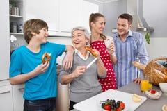 Utveckling som tre tillsammans bor: lycklig familj i köket Royaltyfria Bilder
