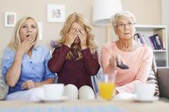 Utveckling tre av kvinnor som håller ögonen på TV Royaltyfri Bild