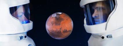 Utvecklingen av Mars, begrepp Två astronaut, en man och kvinnan som ser planeten, fördärvar Arkivfoton