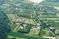 Utvidgning av en stad i norden av Tyskland med liten jordbruksmark, vägar, hus, kommersiella företag och osammanhängande skogsmar arkivbilder